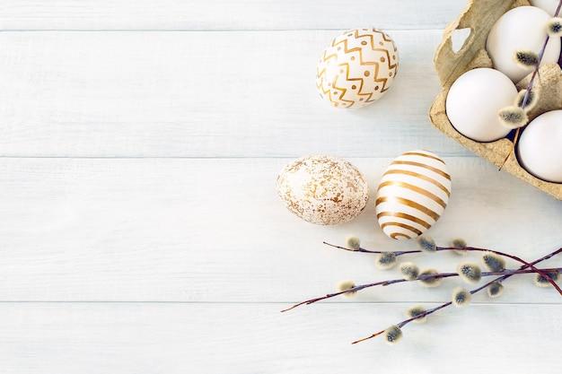 Paasmorgen. beschilderd met gouden patronen kippeneieren in een kartonnen doos met een wilgentak op een tafel close-up.