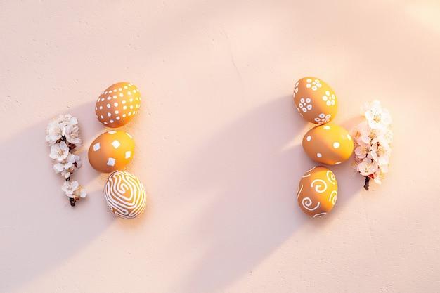 Paasmorgen op het platteland. natuurlijke textuur van klei met warme zonlichttinten. bruine eieren met eenvoudige witte patronen