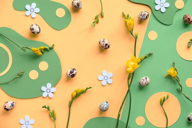 Paassamenstelling in groen en geel. plat lag, top uitzicht met kwarteleitjes, fresia's bloemen.