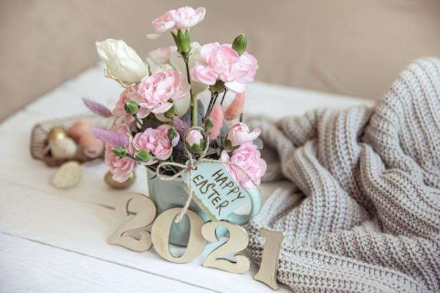 Paasstilleven met verse lentebloemen in een vaas, gebreid met een element en decoratief nummer van het jaar 2021.