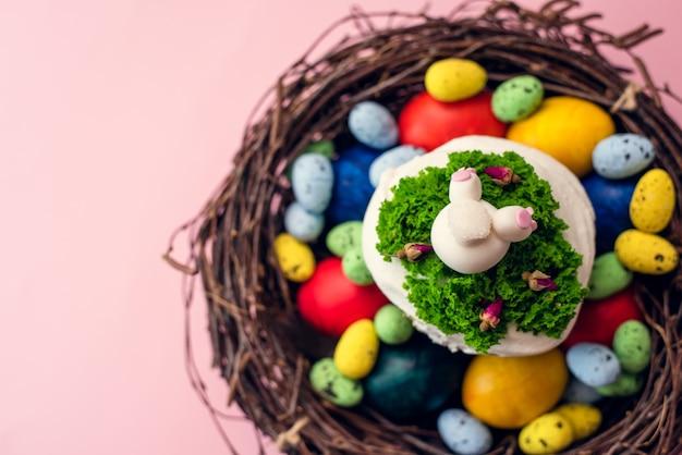 Paastaart versierd met room in de vorm van gras en een beeldje van een konijnenbont in een mand op een roze achtergrond