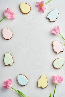 Paastafel met bloemendecor en bord met paaspeperkoek op witte tafel