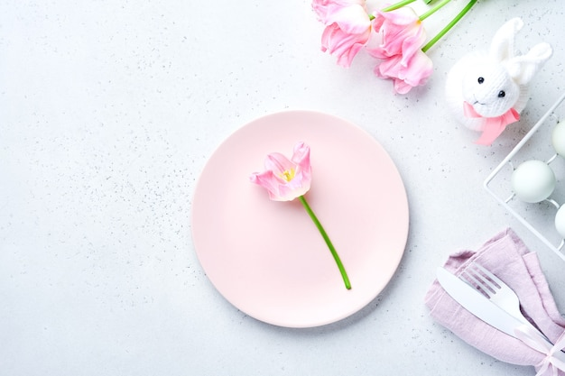Paastafel met bloemendecor op grijze tafel. elegant diner. bespotten. bovenaanzicht.