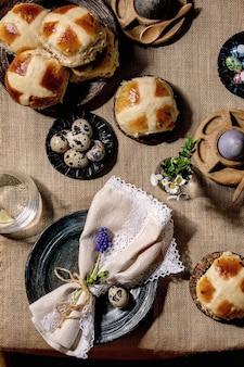 Paastafel-opstelling met gekleurde en chocolade-eieren, warme kruisbroodjes, boeketbloemen, lege keramische plaat met servet,