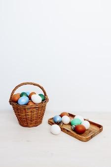 Paasvakantie-eieren in een mand en en op de tradities van de de decoratieskerk van een borddecoratie