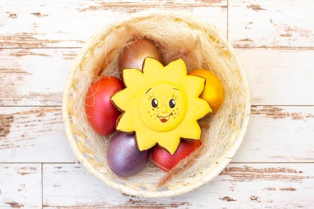 Paasvakantie. gekleurde eieren in een mand. pasen peperkoek koekjes zon. op een lichte houten achtergrond.