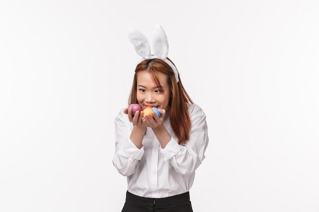 Paasvakantie, viering concept. portret van grappige aziatische vrouw in konijnenoren, hebzuchtig en verbaasd over beschilderde eieren alsof ze mijn kostbare, staande vermaakte witte muur vertelt