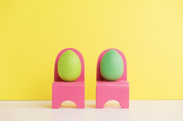 Paasvakantieconcept met schattige eieren leven. verschillende emoties en gevoelens. mooie paareieren die op roze stoelen op gele muur zitten.