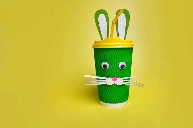 Paasvakantieconcept met schattige groene kartonnen kop koffie, met oren en een konijnengezicht, handgemaakte decoratie voor pasen op een felgele achtergrond