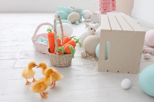 Paasversierde studio met eendjes, wortels en beschilderde grote eieren.