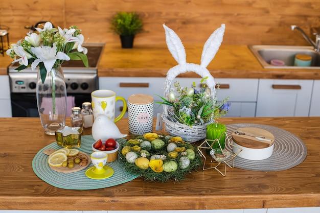 Paasviering op houten aanrecht. geverfde eieren met snacks en mand met konijnenoren op houten aanrecht.