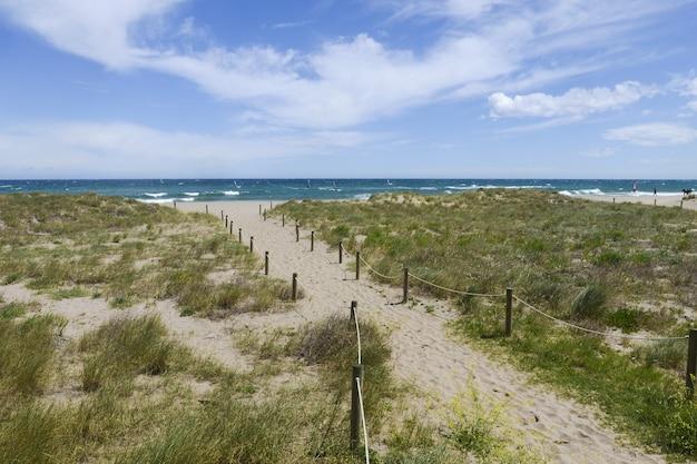Pad aan een kust met een prachtig uitzicht op een oceaan onder een blauwe lucht