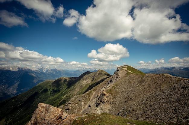 Pad in de alpen leidt langs de bergrug naar het kruis op de top. meer berg
