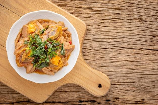 Pad ka prao kai yeow ma, thais eten, basilicum roergebakken eeuws ei en gesneden varkensvlees met knapperige basilicumblaadjes bovenop in keramische plaat en snijplank op rustieke natuurlijke houtstructuur achtergrond, bovenaanzicht