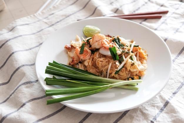 Pad thai, garnalen, inktvis, met chili, limoen en groenten aan de zijkant