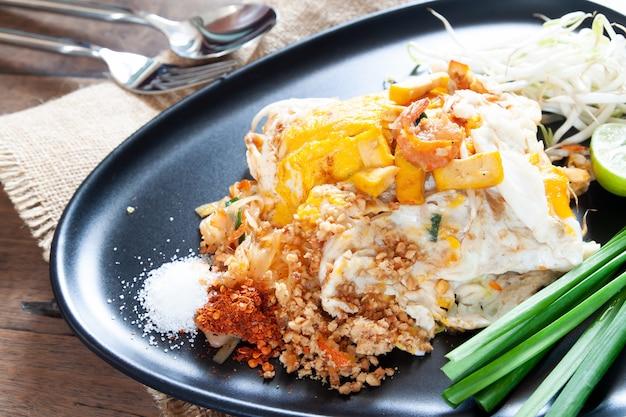 Pad thai of geroerbakte noedels met garnalen en eieren op een zwarte plaat