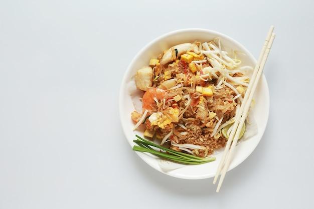 Pad thai roergebakken noodle thaise stijl met varkensvlees tofu en groente op plaat op een witte achtergrond, het favoriete eten in thailand