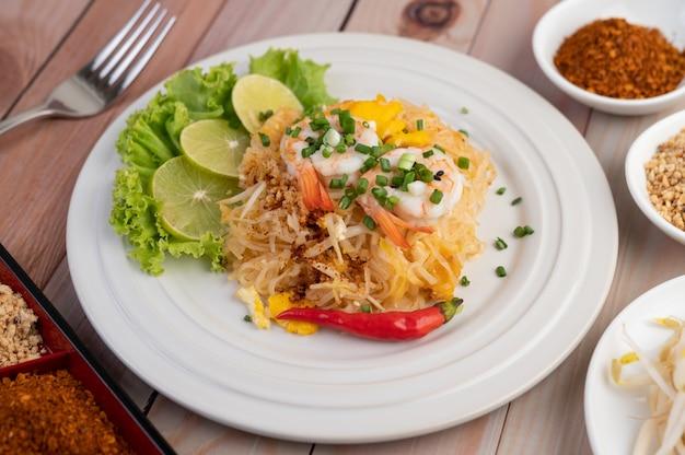 Pad thaise verse garnalen in een witte plaat.