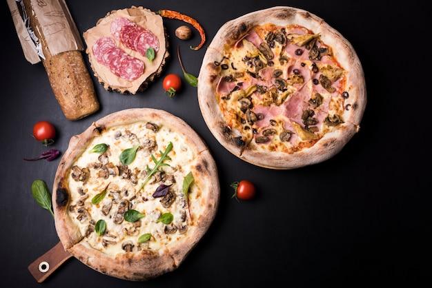 Paddestoel en salamipizza met ingrediënten die over zwarte oppervlakte worden geschikt