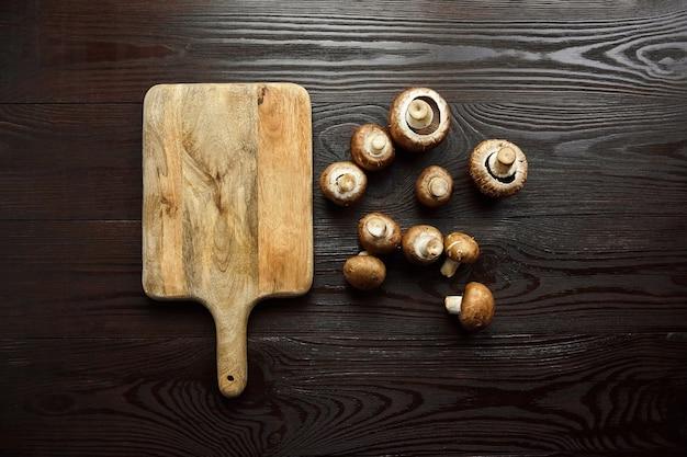 Paddestoelen en snijplank, groep van verse bruine champignons verspreid over een houten achtergrond, bovenaanzicht, platte lat. ongekookt voedselingrediënt