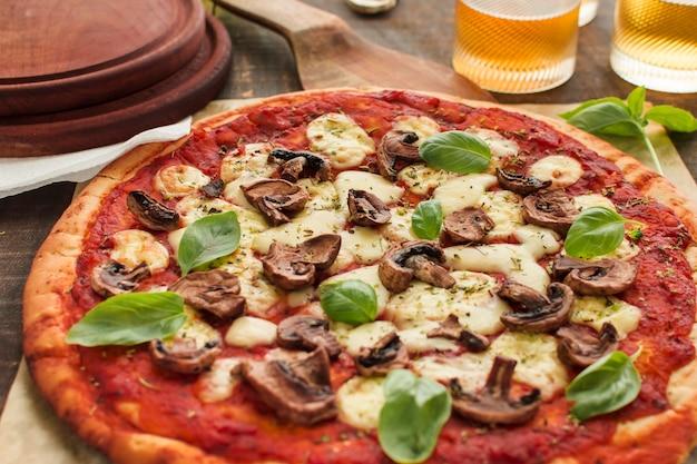 Paddestoelenplakken en basilicumbladeren op pizza met tomatensaus