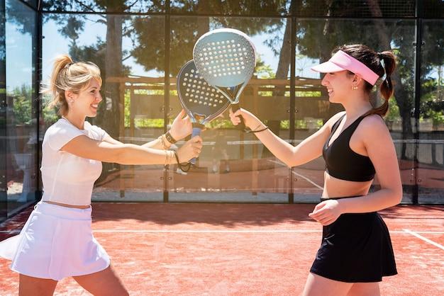 Padeltennisvrouwen spelen in de zomer op een buitenbaan