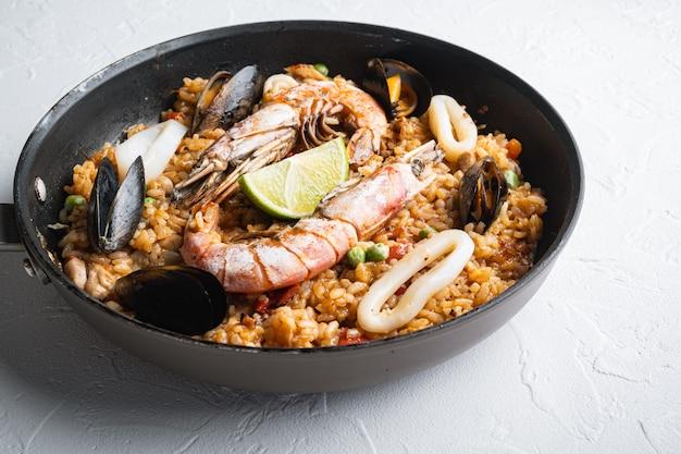 Paella met zeevruchten en kip op witte achtergrond