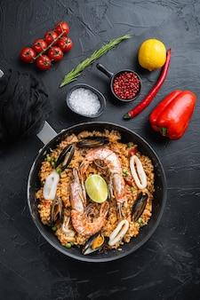 Paella traditionele spaanse schotel geserveerd in koekenpan, op zwart gestructureerd oppervlak