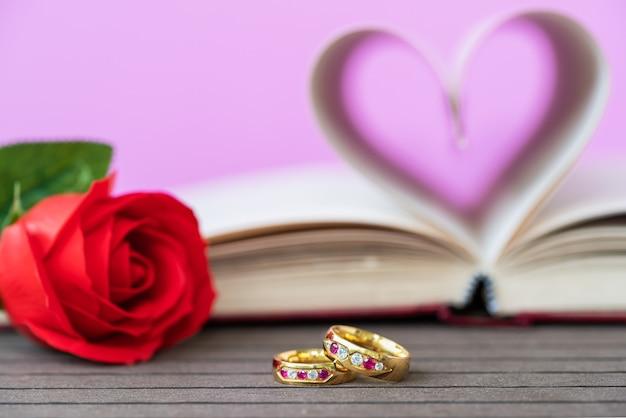 Pagina's van boek gebogen in hartvorm met rode roos