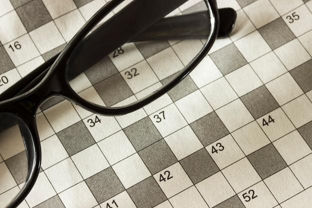 Pagina's van het tijdschrift met de kruiswoordpuzzel en bril