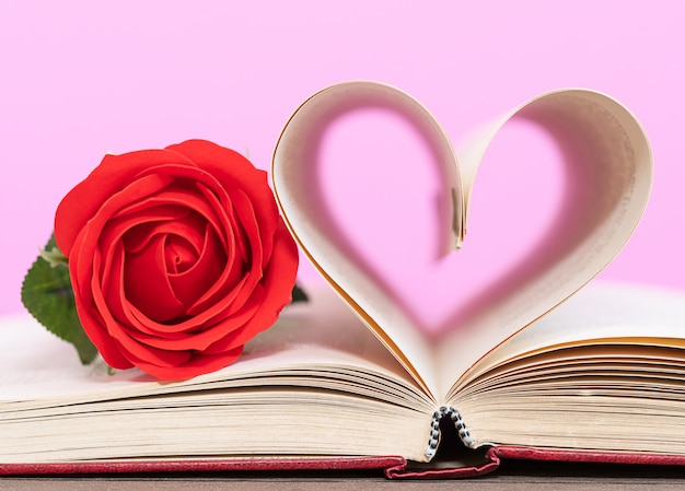 Pagina van boek gebogen hartvorm en rode roos