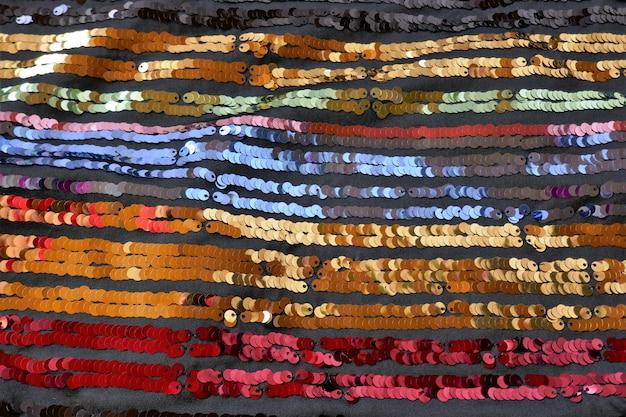 Pailletten macro achtergrond gestreepte kleurrijke achtergrond gestreepte pailletten stof met pailletten glanzende stofschubben achtergrond