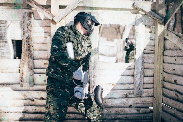 Paintballgevecht, schermutseling in het winterbos, paintball. extreme sport, actief militair spel