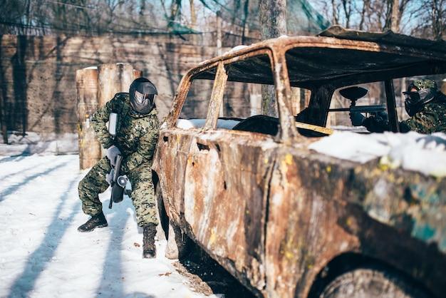 Paintballgevecht, verbrande auto in winterbos