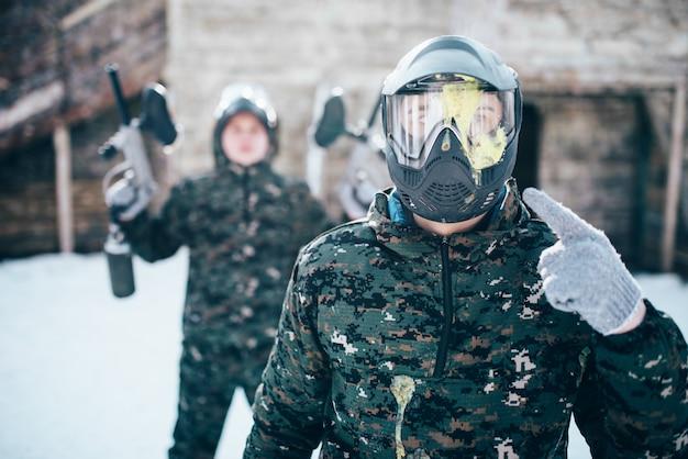 Paintballspeler wijst vinger naar spetterde masker, team na winterse strijd. extreme sportgame, soldaten in speciaal uniform, paintball
