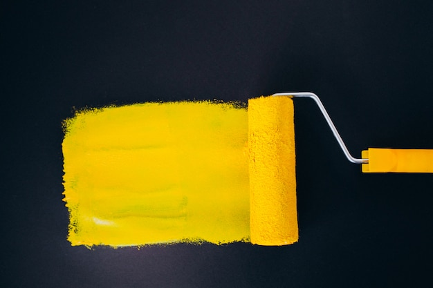 Paintroller voor reparaties geïsoleerd op zwarte achtergrond in gele verf