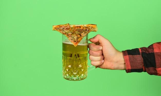 Pak aan. mannenhand houdt glas bier en plak pizza vast. perfecte rust in de pub. pizza eten en bier drinken. eindelijk pizzatijd. pizza is beter wanneer gedeeld. pizzeria-restaurant. afhaal optie.