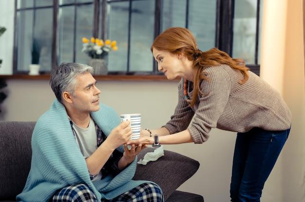 Pak aan. positieve vrolijke vrouw die lacht terwijl ze thee brengt voor haar man