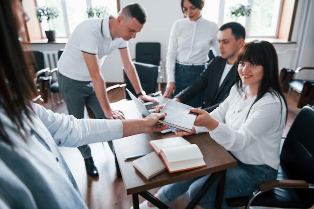 Pak dit notitieblok. mensen uit het bedrijfsleven en manager werken aan hun nieuwe project in de klas