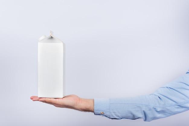Pak melk op mannelijke palm op witte muur. kopieer ruimte, bespot