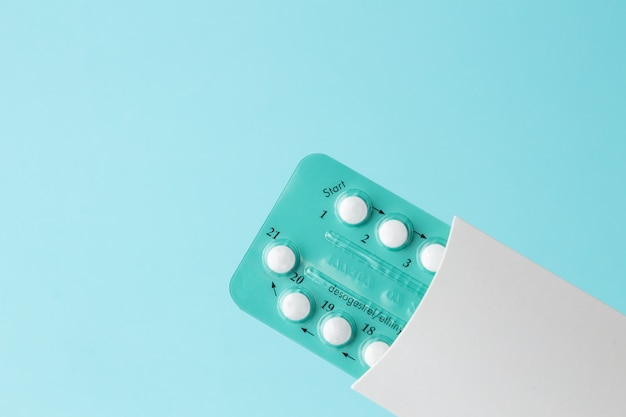 Pak orale anticonceptiepillen met instructies, blister in wit geval op blauw