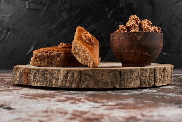 Pakhlava en noten op een houten bord.
