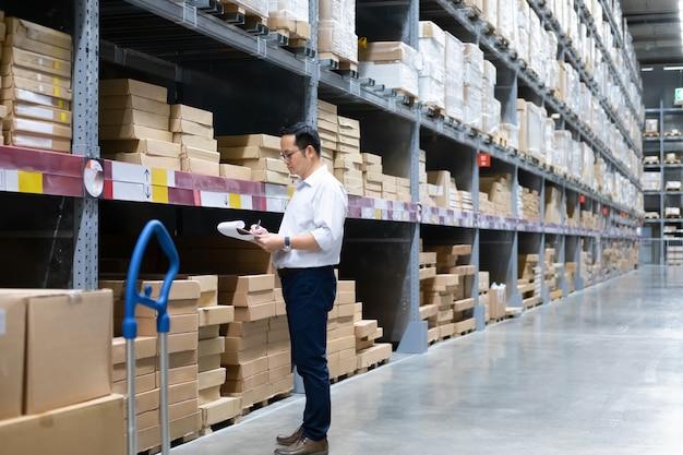 Pakhuisarbeider die goederen controleren bij pakhuis.