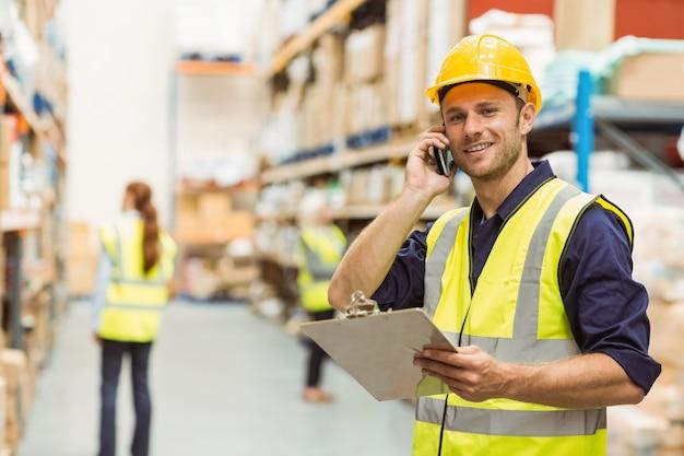 Pakhuisarbeider die op het klembord van de telefoonholding spreken