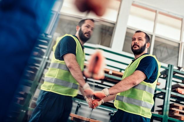 Pakhuisarbeiders die roestvrij staal inox plaatwerk in fabriek dragen
