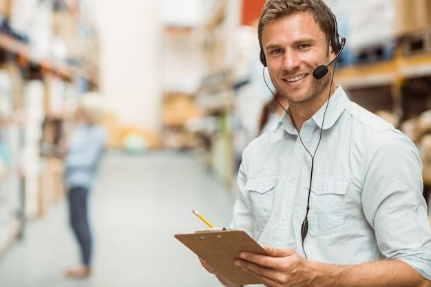 Pakhuismanager die hoofdtelefoon dragen die op klembord schrijven