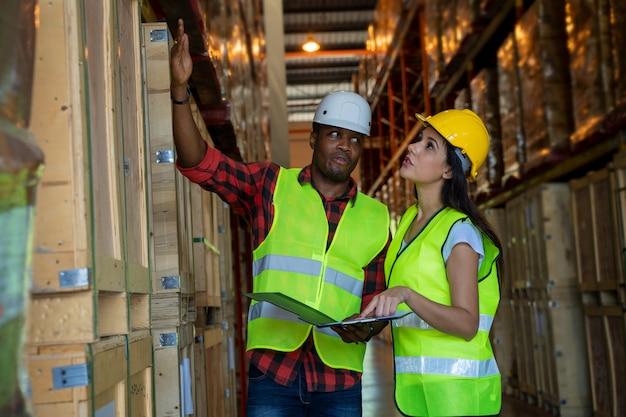 Pakhuismanager en pakhuisarbeider die helm met klembord dragen die producten controleren over leveringsschema in industriële opslagruimte.