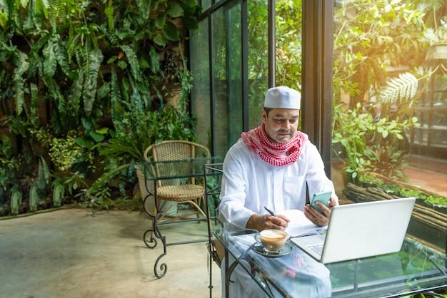 Pakistaanse moslim arabische man hand houden slimme mobiele telefoon en laptop op tafel