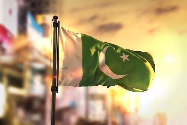 Pakistan vlag tegen stad wazige achtergrond bij zonsopgang achtergrondverlichting