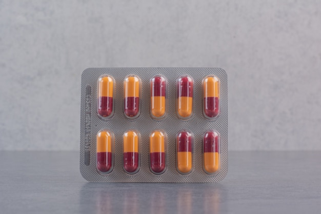 Pakje antibiotica pillen op marmeren tafel.